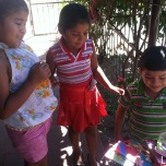 Three siblings getting to pick out their notebooks in Masaya, Nicaragua